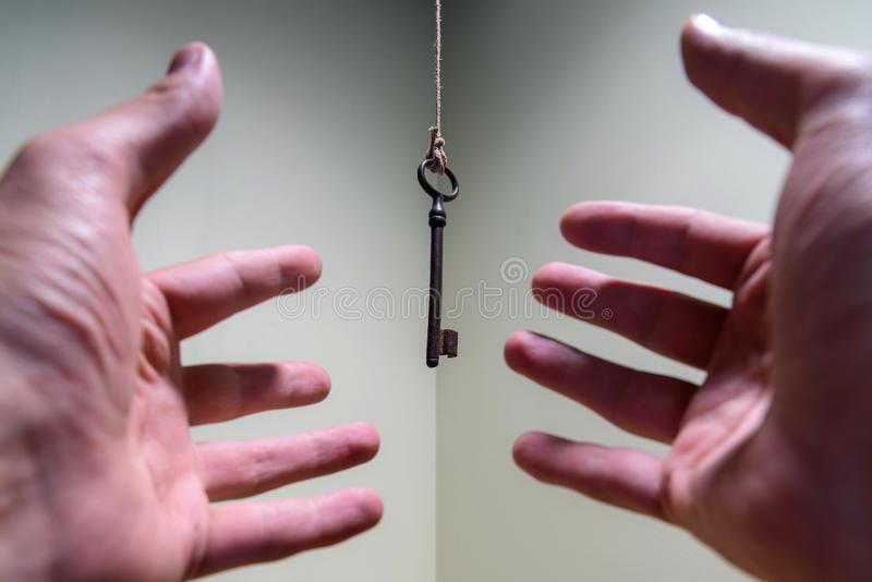 People hands reaching for vintage key hanging on a string. Business success freedom concept concept for aspirations, achievement. And incentive royalty free stock images