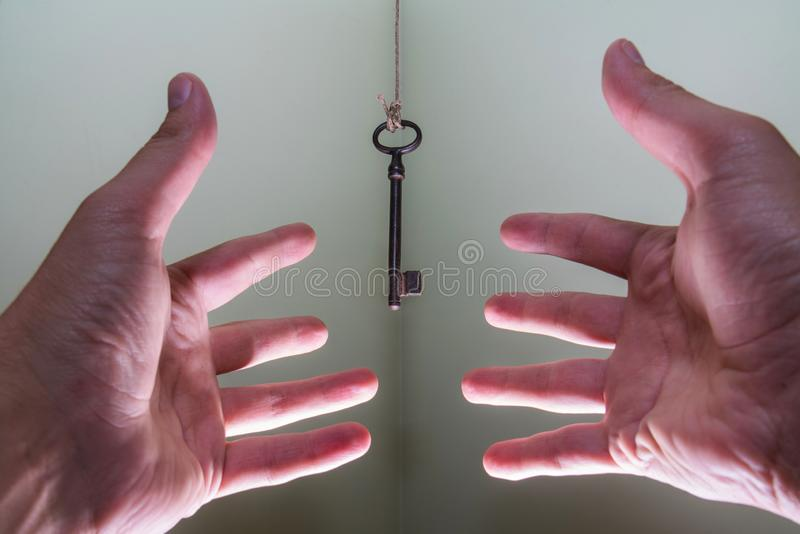 People hands reaching for vintage key hanging on a string. Business success freedom concept concept for aspirations, achievement. And incentive stock photo