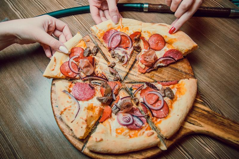 People Hands Taking Slices Of Pizza Margherita. Pizza Margarita and Hands close up over black background. royalty free stock photos