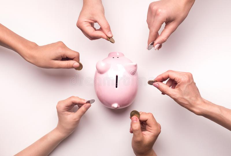 People hands throwing coins in piggy bank for crowdfunding. Togetherness concept. People hands throwing coins in piggy bank for crowdfunding, white background royalty free stock photography