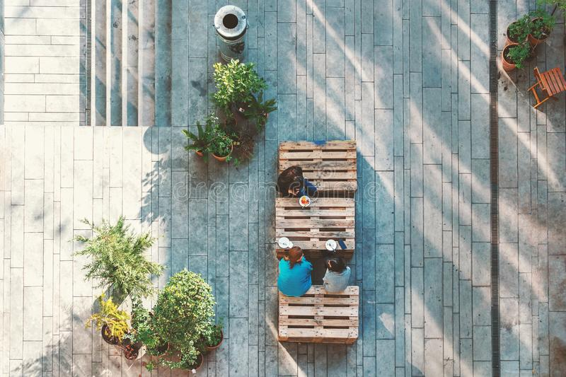 People hanging out in the garden, sitting on the pallets eating cakes. View from above. Concept. People hanging out in the garden, sitting on the pallets eating stock images