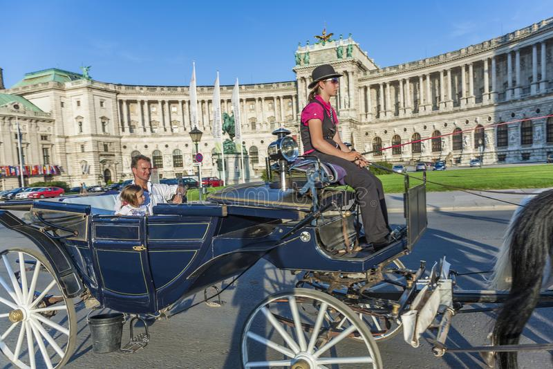 People have a ride in the horsedrawn carriage called fiaker and passing the Vienna Hofburg stock images