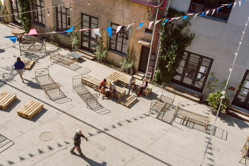 People having fun in grunge area of city with artistic galleries and weird benches stock image