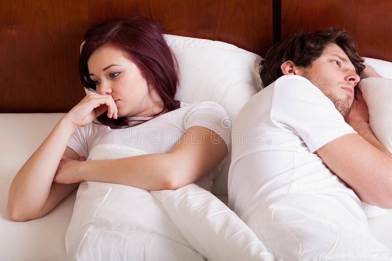 People having marital problems. People lying together but separately because of marital problems royalty free stock photo