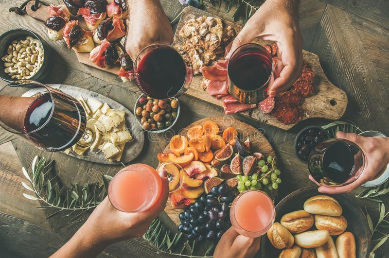 People having party sitting at table set with wine snacks. Flat-lay of friends eating and drinking together. Top view of people having party, gathering, dinner stock photos