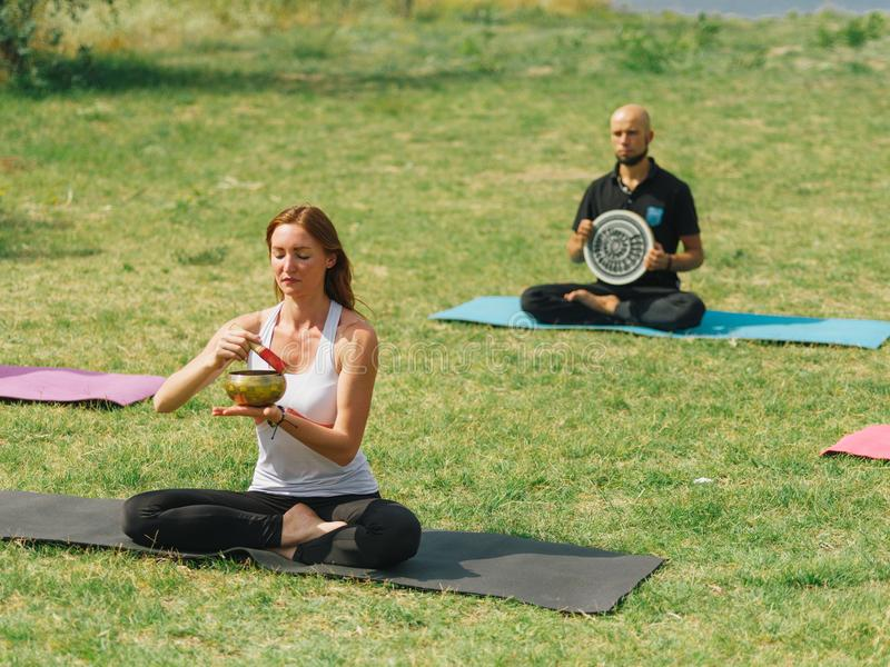 Fitness team are exercising in the park. Yoga concept. royalty free stock image