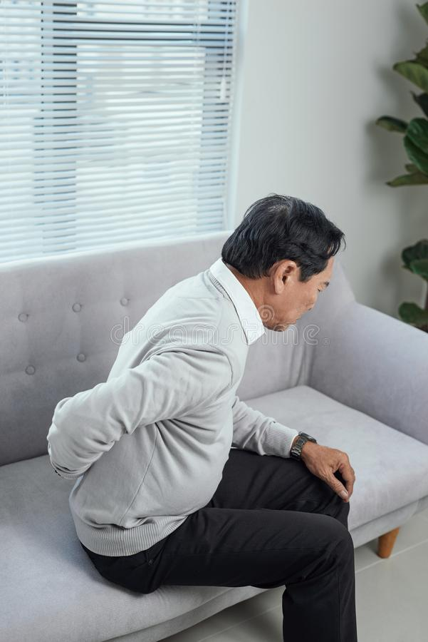 People, healthcare and problem concept - unhappy senior man suffering from pain in back or reins at home stock image
