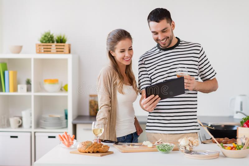 Happy couple with tablet pc cooking food at home. People and healthy eating concept - happy couple with tablet pc computer and non alcoholic wine cooking food at stock photos