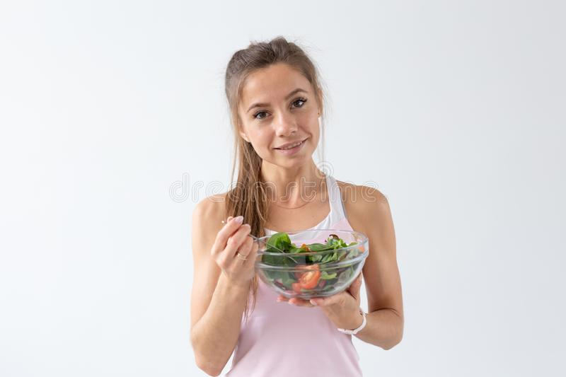 People, healthy lifestyle and fitness concept - Beautiful woman sitting on the floor after workout and eating healthy. Salad stock photo