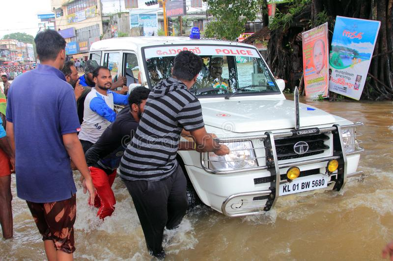 People help a vehicle to cross the flood water. In the road on August 17,2018 in Pathanamthitta,Kerala, India. Kerala was badly affected by the floods during royalty free stock images