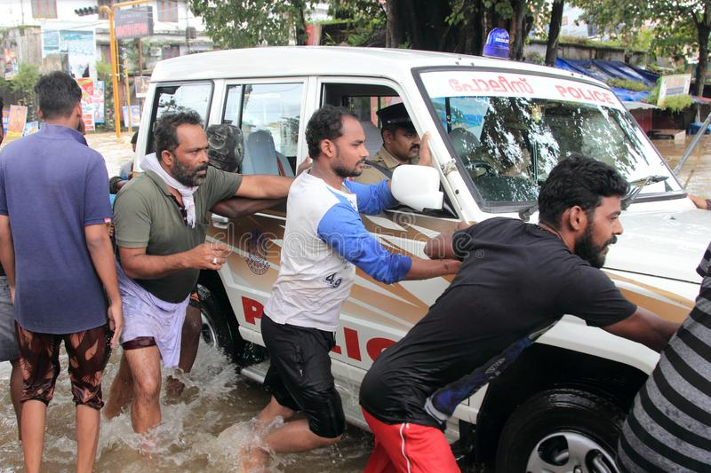 People help a vehicle to cross the flood water. In the road on August 17,2018 in Pathanamthitta,Kerala, India. Kerala was badly affected by the floods during royalty free stock photography