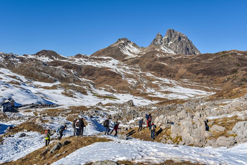 People hikers moving along the mountain slope in French Atlantic Pyrenees. The early winter landscape of Portalet mountain pass royalty free stock photo