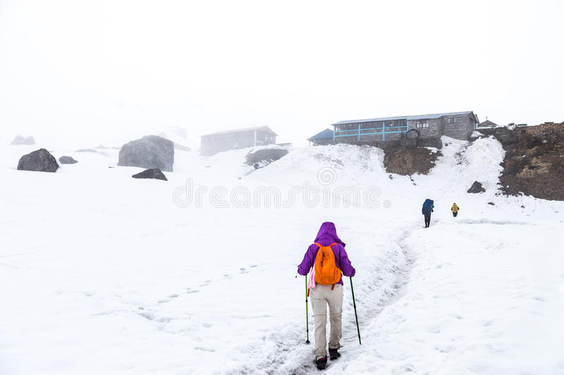 People hiking on snow trail towards base camp stock images
