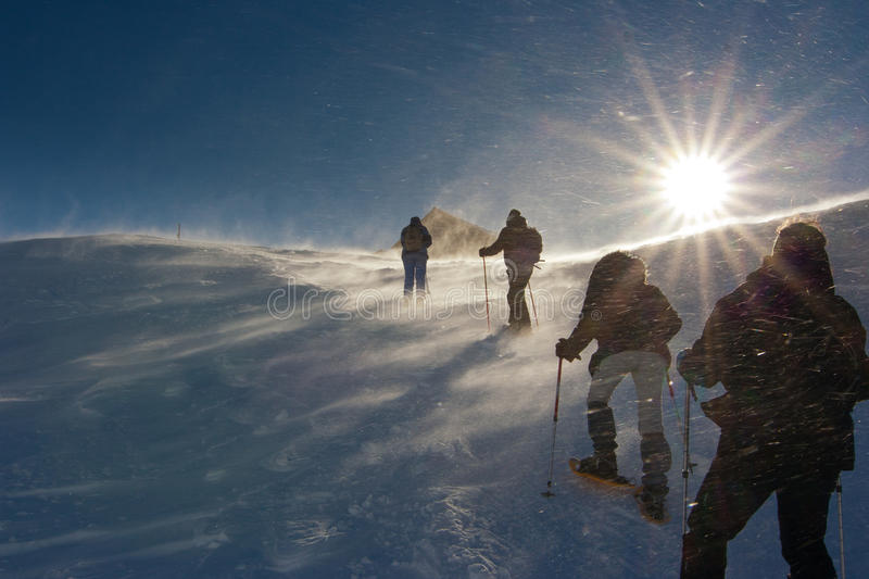 People hiking on the snow in a wind storm. People hiking towards the top of the hill on the snow in a wind storm stock photos
