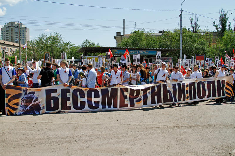 People hold banner of Immortal regiment and portraits of their relatives on Victory day in Volgograd stock images