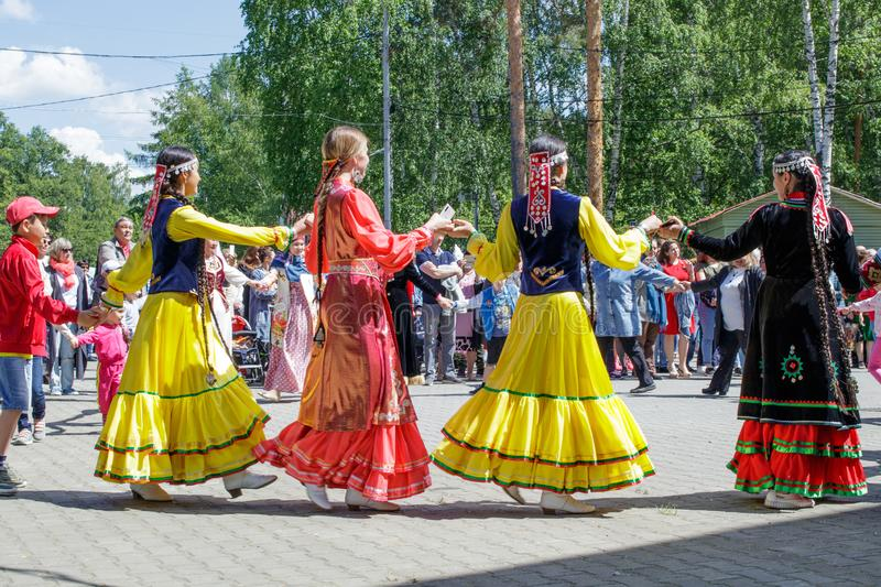 People hold hands, dancing in a circle. The annual national holiday of the Tatars and Bashkirs Sabantuy in the city park royalty free stock photo