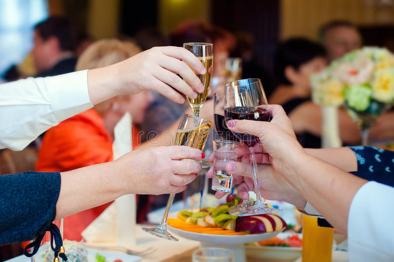 People hold in hands glasses with white champagne. Toasting at the wedding party stock photo