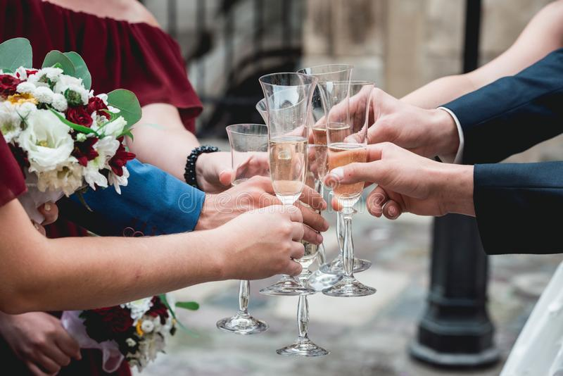 People hold in hands glasses with white wine. wedding party. stock images
