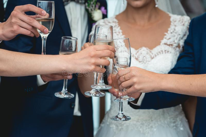 People hold in hands glasses with white wine. wedding party. stock photos