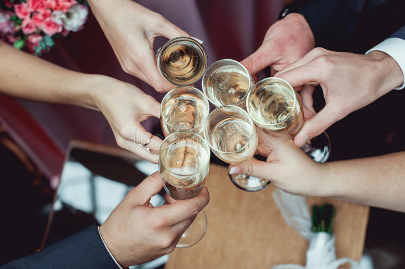 People hold in hands glasses with white wine. wedding party. stock photo
