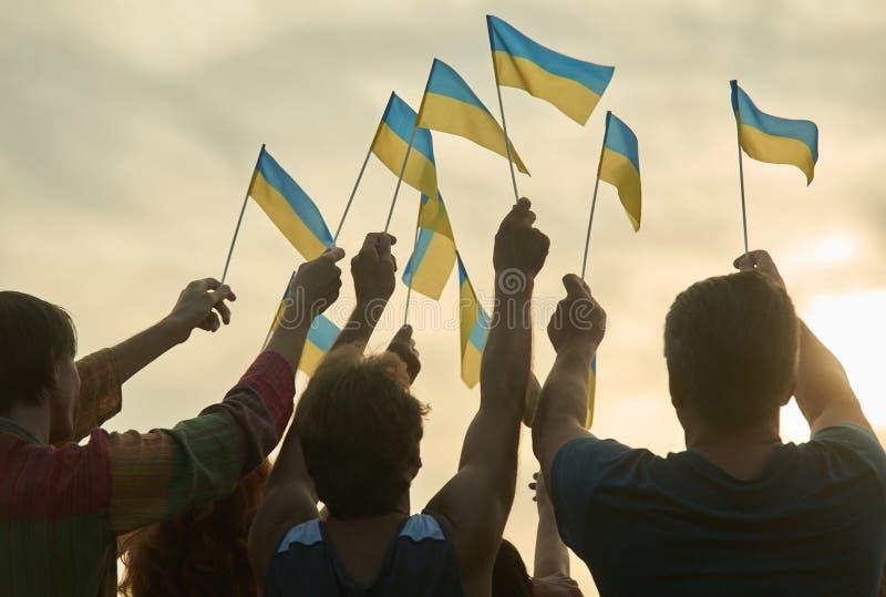 People hold ukrainian flags. Silhouette of patriotic ukrainian crowd, rear view. Gloving evening sun background stock photo