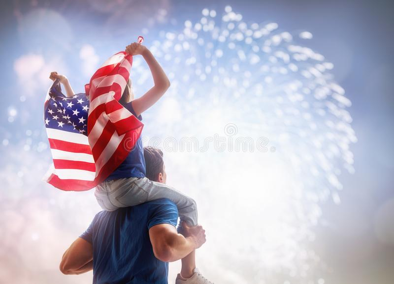 People holding the Flag of the USA. Patriotic holiday. Child sitting on shoulders of her father and holding the Flag of the USA. America celebrate 4th of July royalty free stock photography