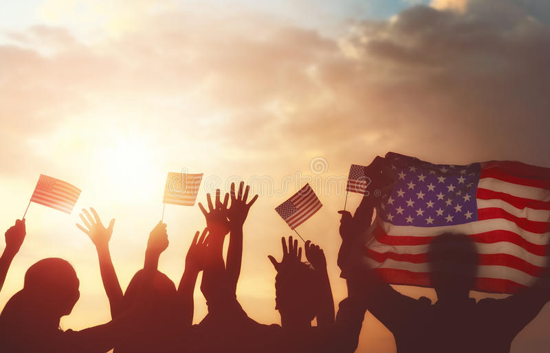 People holding the Flag of USA. Patriotic holiday. Silhouettes of people holding the Flag of USA. America celebrate 4th of July royalty free stock images