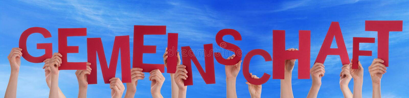 People Holding German Word Gemeinschaft Means Community Blue Sky. Many Caucasian People And Hands Holding Red Letters Or Characters Building The German Word royalty free stock photography