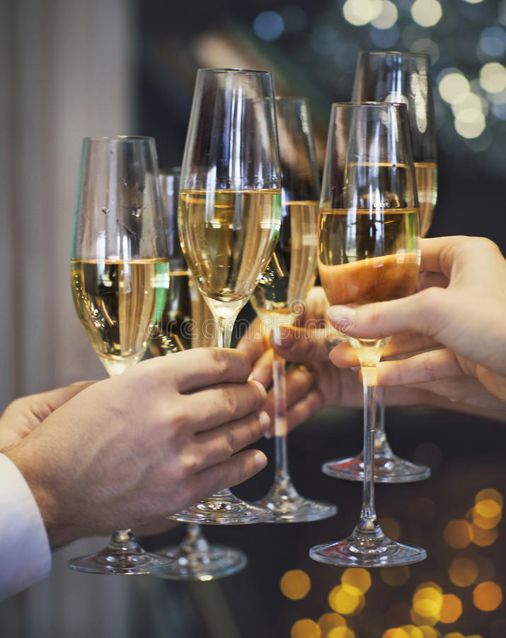 People holding glasses of champagne making a toast. Celebration. People holding glasses of champagne making a toast. DOF. Natural light. Photo in motion. Toned royalty free stock images