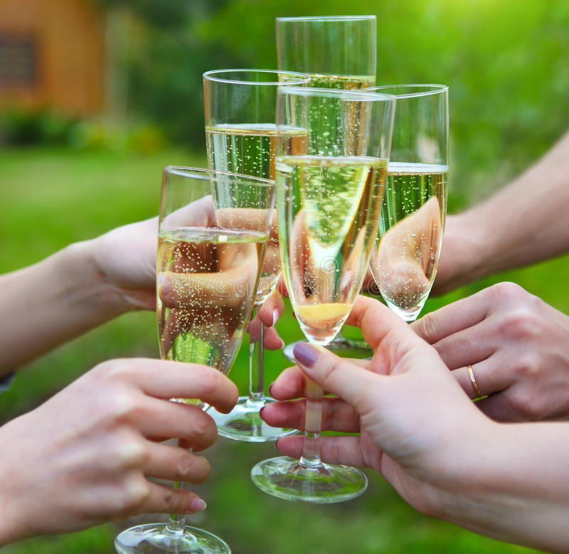 People holding glasses of champagne making a toast outdoors. Celebration. People holding glasses of champagne making a toast outdoors royalty free stock images