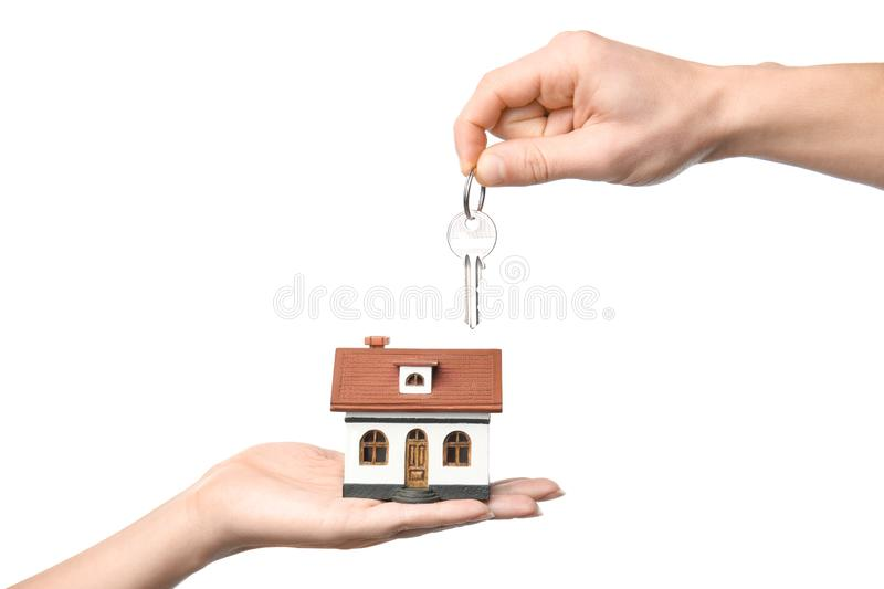 People holding key and house model on white background. Closeup royalty free stock photo