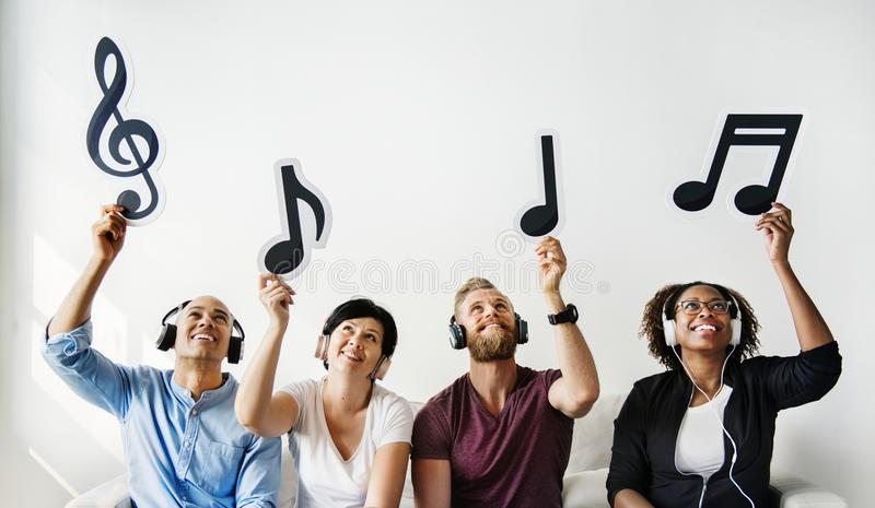 People holding musical notes icons stock images