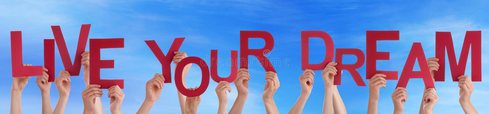 People Holding Red Word Live Your Dream Blue Sky royalty free stock photo