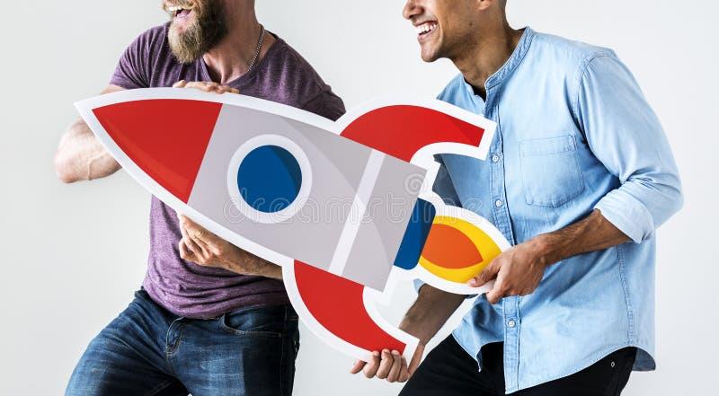 People holding rocket ship icon stock photo
