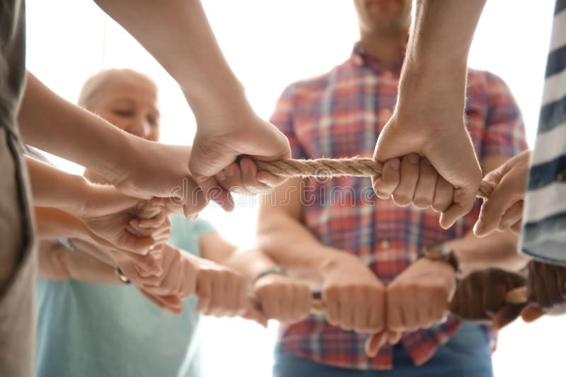 People holding rope together on light background, closeup. Unity concept royalty free stock photos