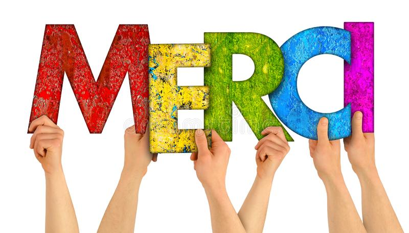 People holding up colorful rainbow wooden letter with the french word Merci english traslation: thank you isolated white stock images