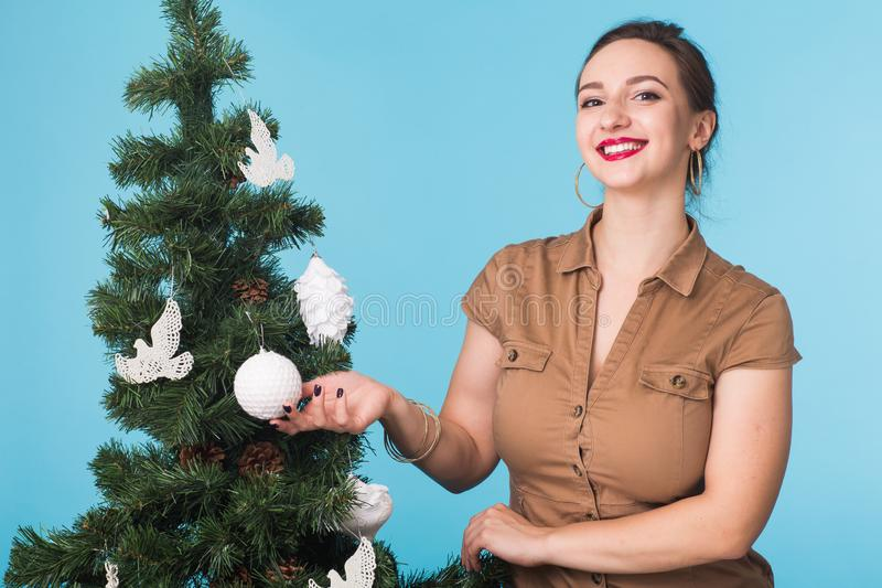 People, holidays and celebrations concept - young woman with christmas tree on blue background. People, holidays and celebrations concept - woman with christmas royalty free stock photo