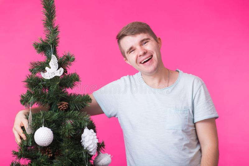 People, holidays and christmas concept - young smiling man near christmas tree on pink background royalty free stock photos