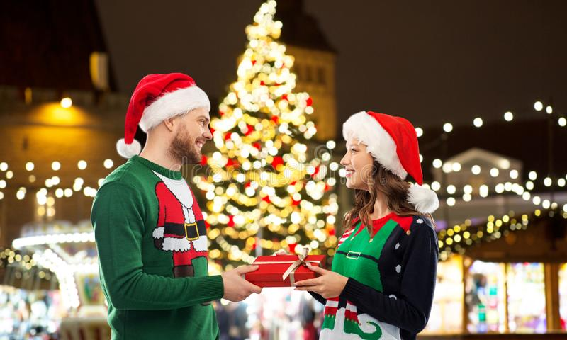 Happy couple with gift at christmas market. People and holidays concept - happy couple in santa hats and ugly sweaters with gift box over christmas market lights stock image