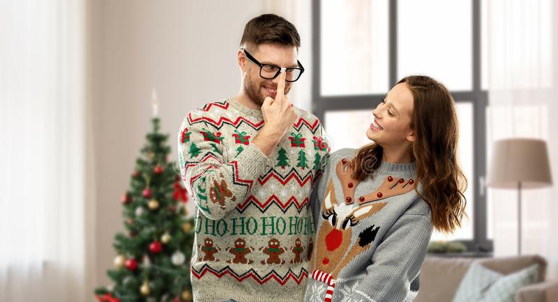 Happy couple in christmas ugly sweaters at home royalty free stock photography