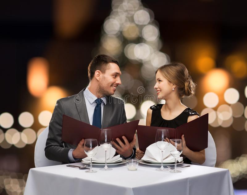 Smiling couple with menus at christmas restaurant stock image