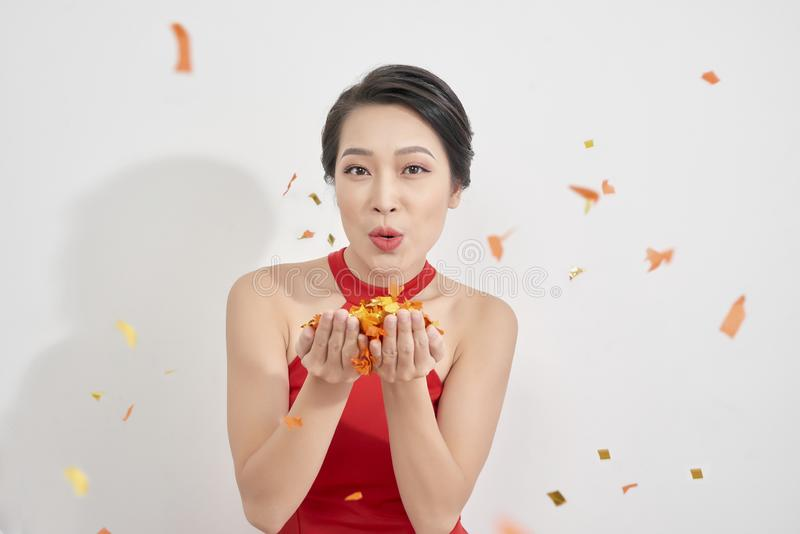 People, holidays, gesture and glamour concept - happy young woman or teen girl in fancy dress and confetti at party sending blow. Kiss stock image