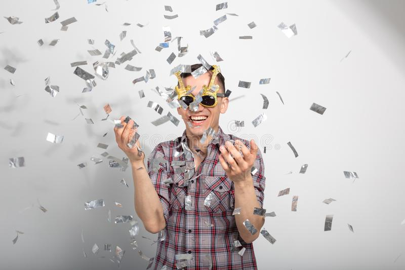 People, holidays and party concept - Man with funny face in plaid shirt with confetti royalty free stock photos