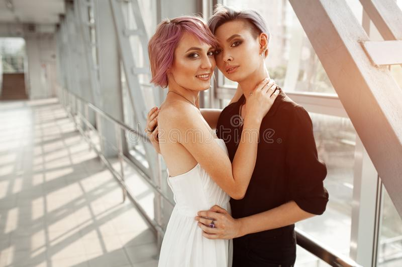 People, homosexuality, same-sex marriage, travel and gay love concept. Close up of happy women couple hugging over metall bridge. Two girlfriend walking royalty free stock image