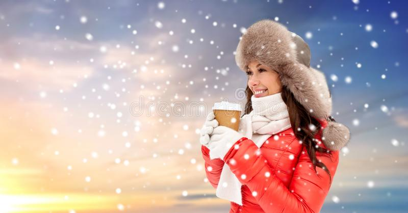 Woman in winter fur hat with coffee over snow royalty free stock photos