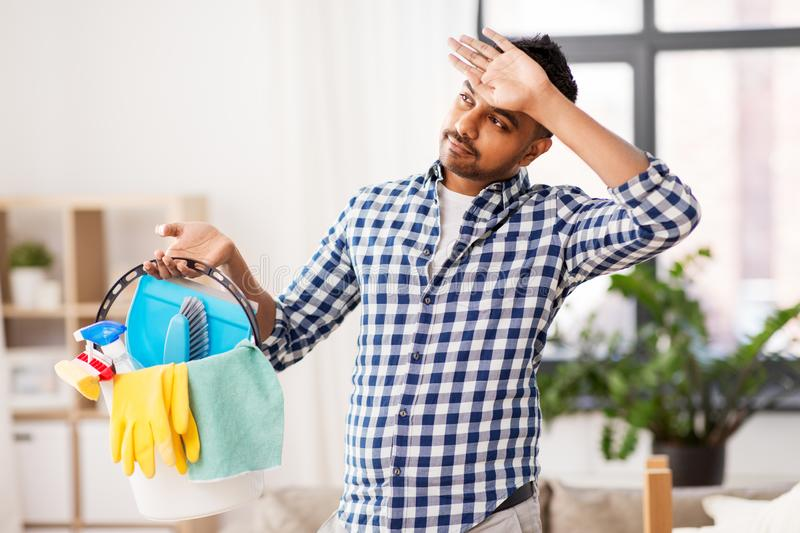 Tired man with bucket of cleaning stuff at home stock image