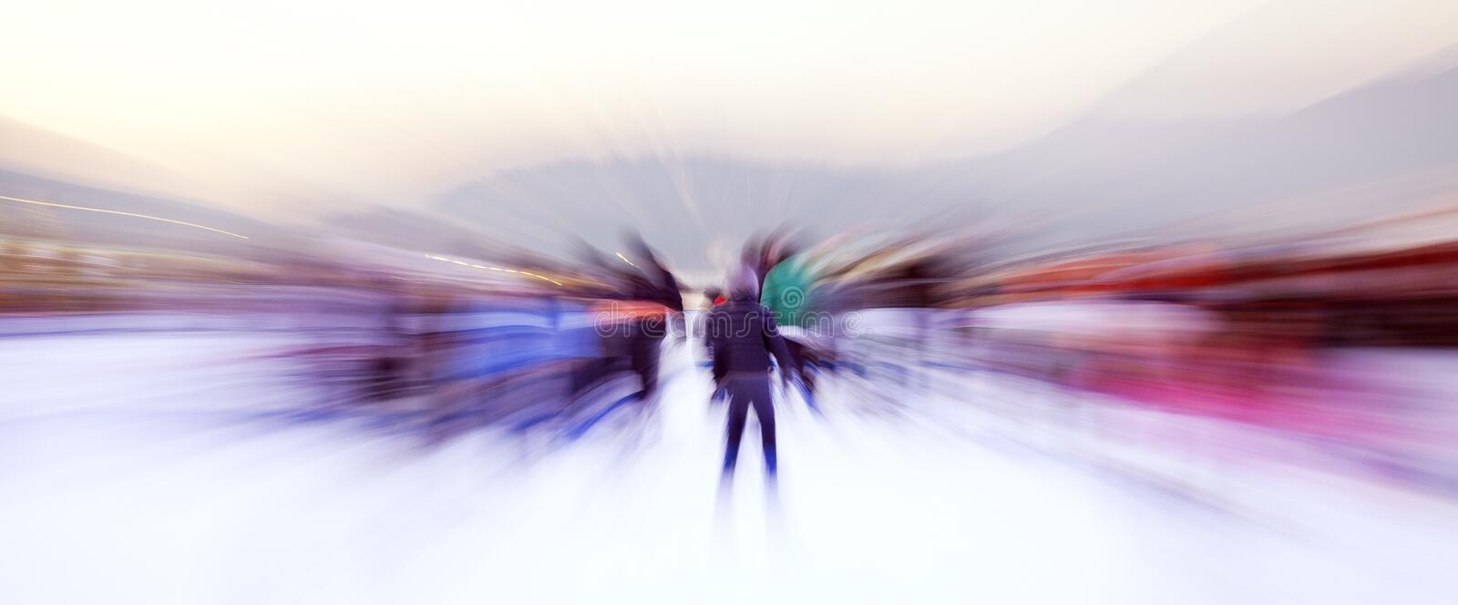 People on a ice rink, blurred motion. Color image. Some people are skating on a ice rink, during the holiday in Xmas time royalty free stock photography