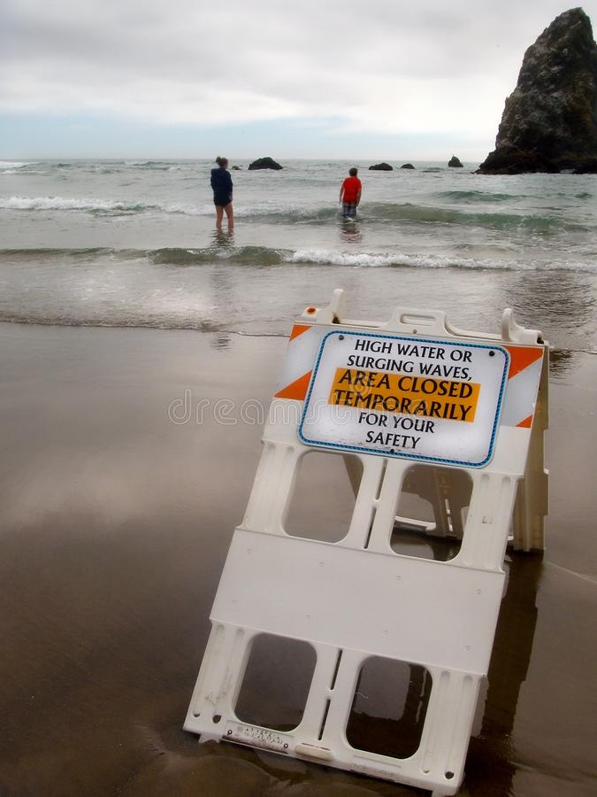 Warning Sign Area Closed Beach High Water Surge Waves. People ignore warning sign of dangerous high water surges at Cannon Beach, Oregon. Area has reported royalty free stock photography