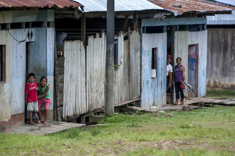 People at Indiana in Peru. People stand at the entrance to their wooden houses in the Amazon River town of Indiana in Peru royalty free stock image