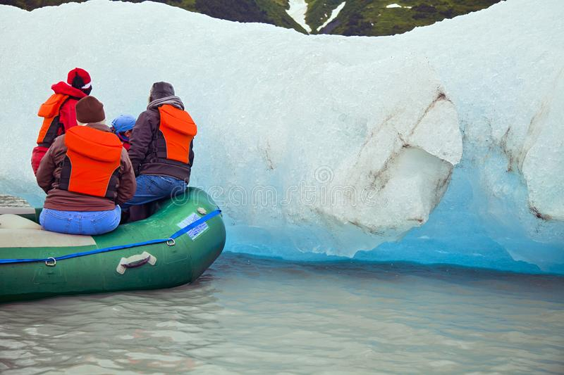 PEOPLE ON INFLATABLE RAFT INSPECTING A GLACIER ICE FLOE royalty free stock photos